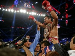 Manny Pacquiao, from the Philippines, raises his arms while wearing the champion's belt as he celebrates winning his WBO international welterweight title fight against Brandon Rios of the United States, Sunday, Nov. 24, 2013, in Macau. Pacquiao defeated Rios by unanimous decision on Sunday, returning to his winning ways after consecutive losses. (AP Photo/ Vincent Yu)