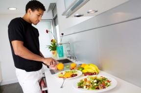 Handsome black man preparing salads in a modern kitchen.