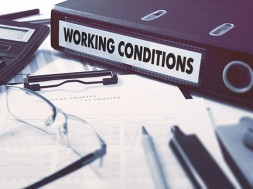 Working Conditions - Office Folder on Background of Working Table with Stationery, Glasses, Reports. Business Concept on Blurred Background. Toned Image.