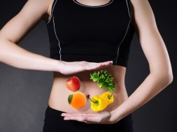 Vegetables and fruits on a background of a female belly closeup .