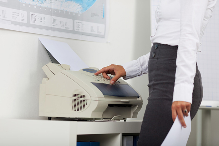 Midsection of businesswoman using copy machine in office