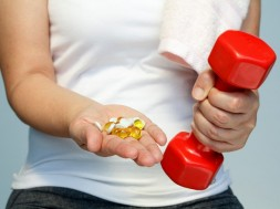 sport and diet concept - woman hand with vitamins and medication